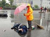 交警和环卫工给倒地男子撑伞