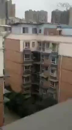 女子悬坐在高楼雨罩上,命悬一线,施救人员抓住其头发将其救起!