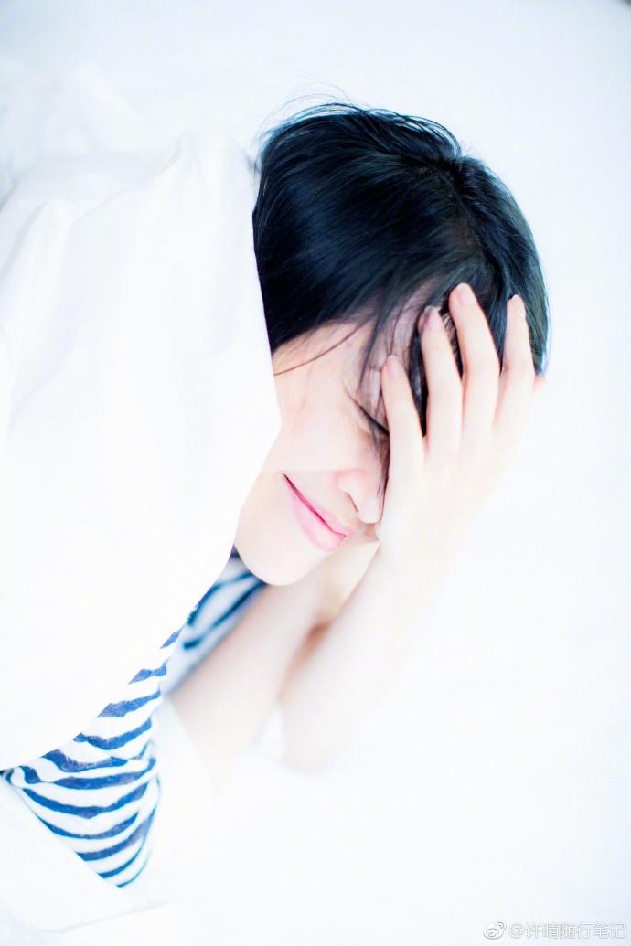 """""""照片中的许晴一身宽松的条纹t恤,黑色短发随意散乱着,白色的被子兜头"""